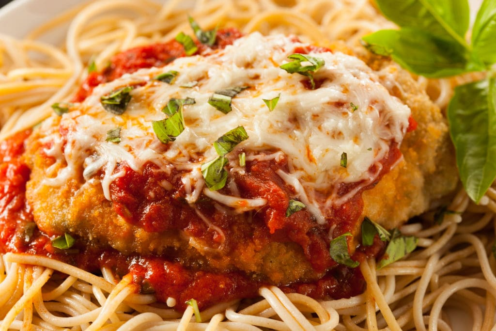 This Chicken Parmigiana recipe is so juicy!  The chicken is moist inside, and crispy on the outside!  It's covered in tomato sauce, melted provolone, Parmesan cheese and Italian spices.  Your family will LOVE this delicious Italian classic!