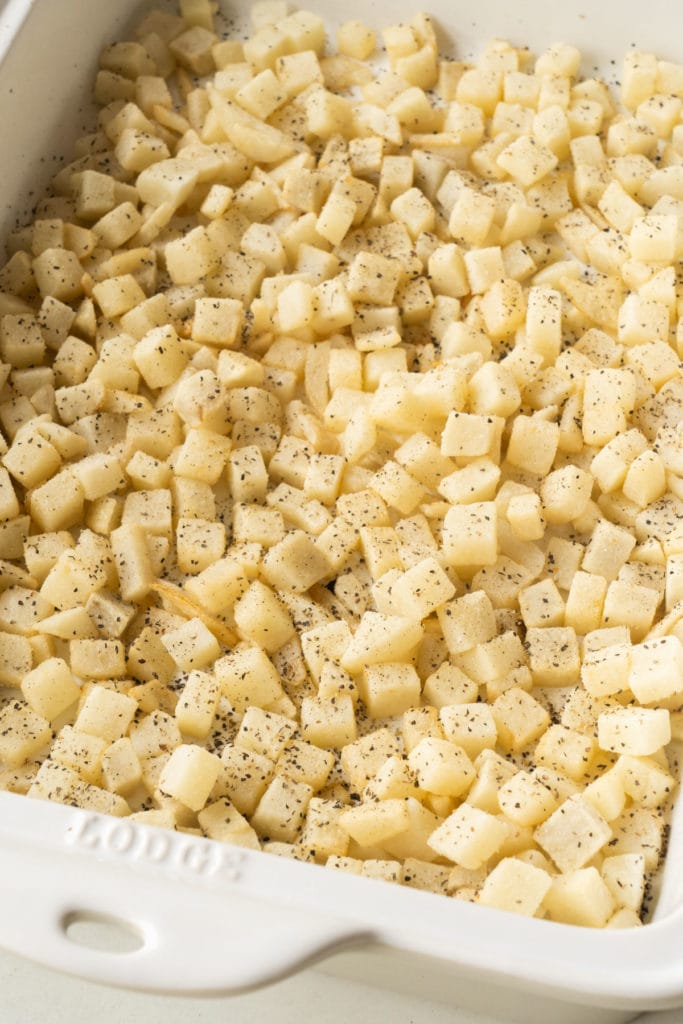hash browns with salt and pepper in baking dish