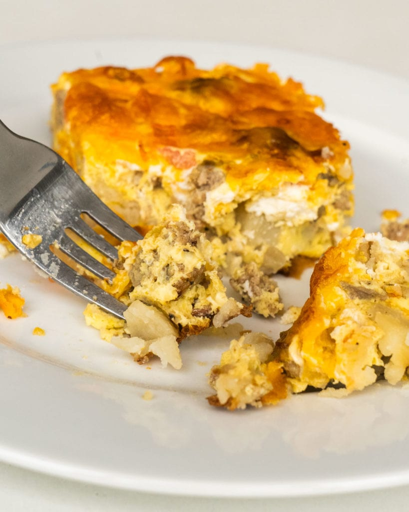 fork cutting up slice of breakfast casserole, eggs and sausage on fork