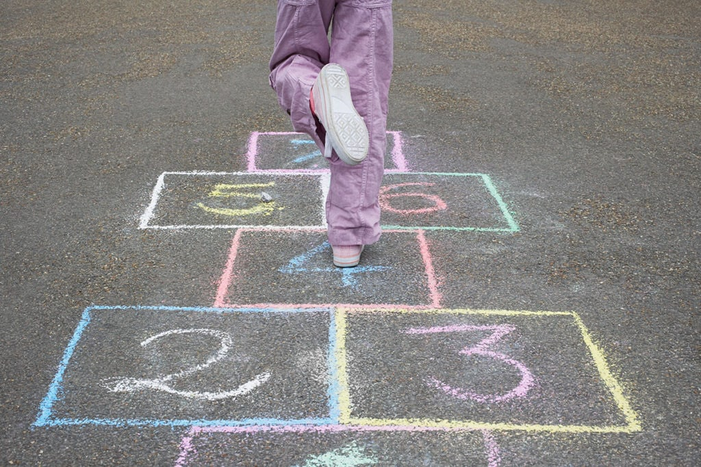 Little girl playing hopscotch outside