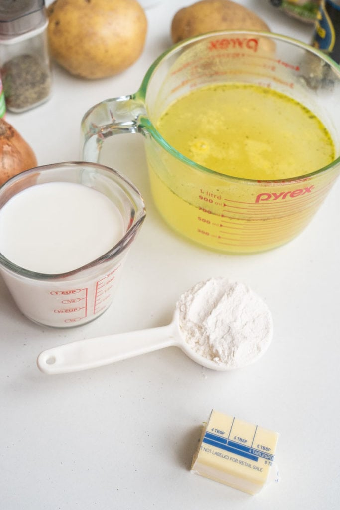 flour, milk and chicken broth on white table