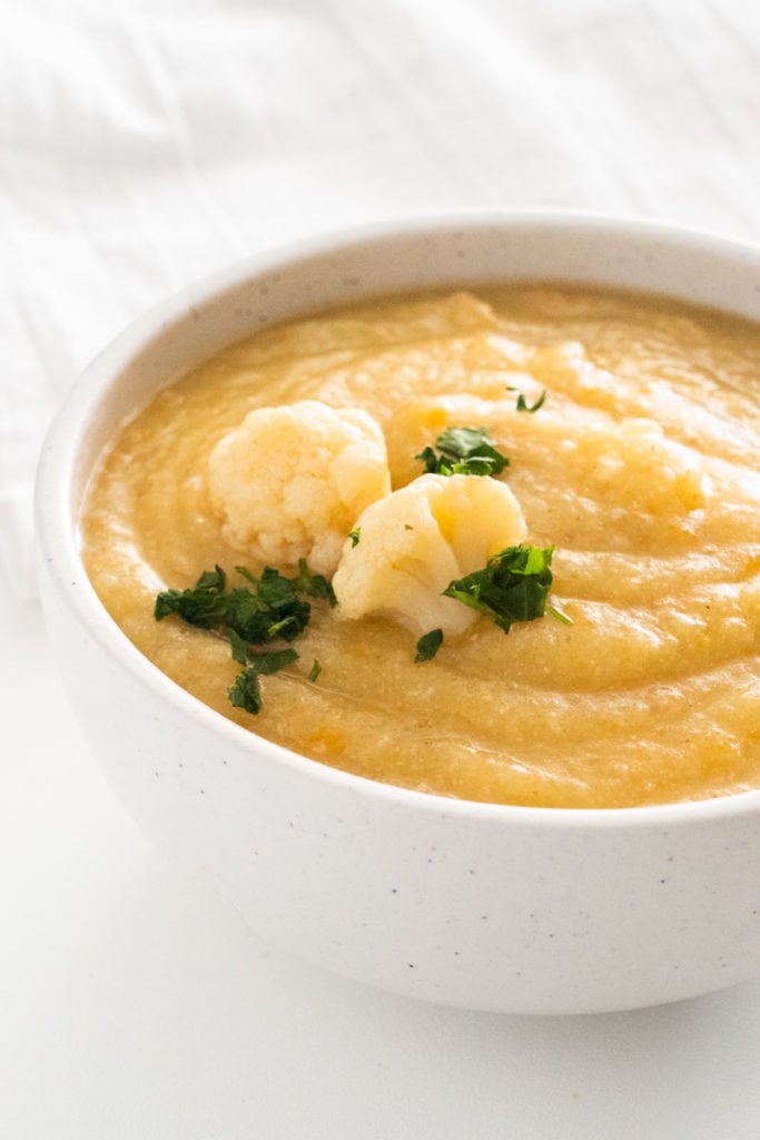 Healthy Vegan Cauliflower Soup made in the crockpot.  It's easy, throw the ingredients in the slow cooker and cook for 4 hours!  Only 150 calories a serving! Enjoy this creamy, delicious Cauliflower Soup for dinner!