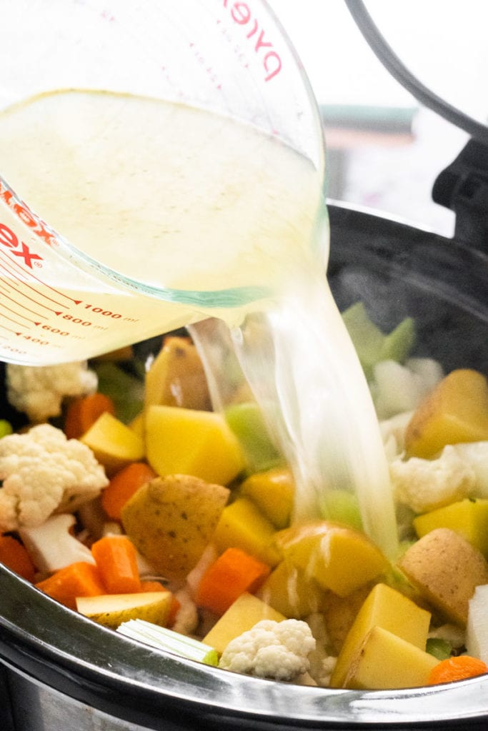 vegetable broth being poured into crockpot