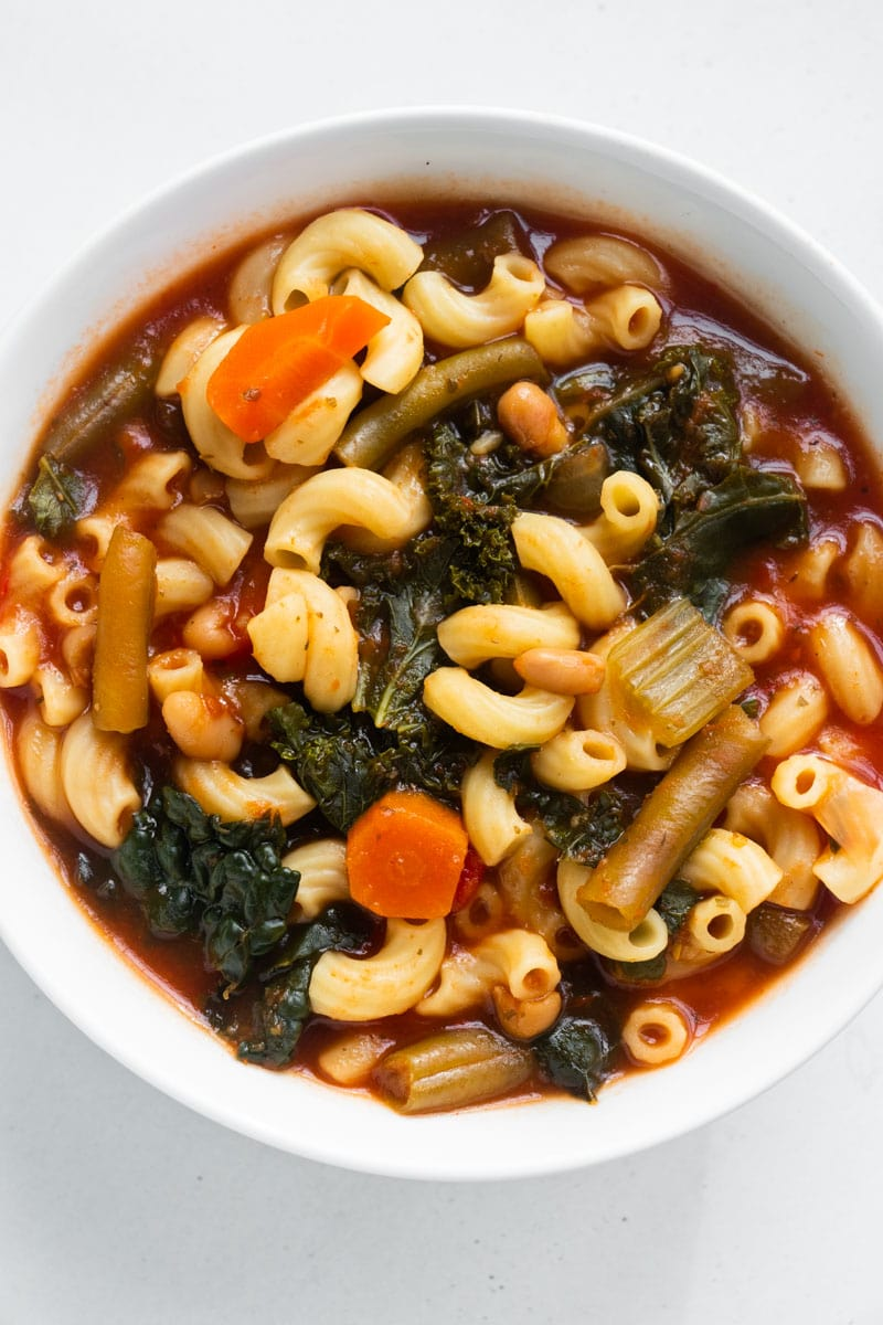 minestrone soup with green beans in white bowl