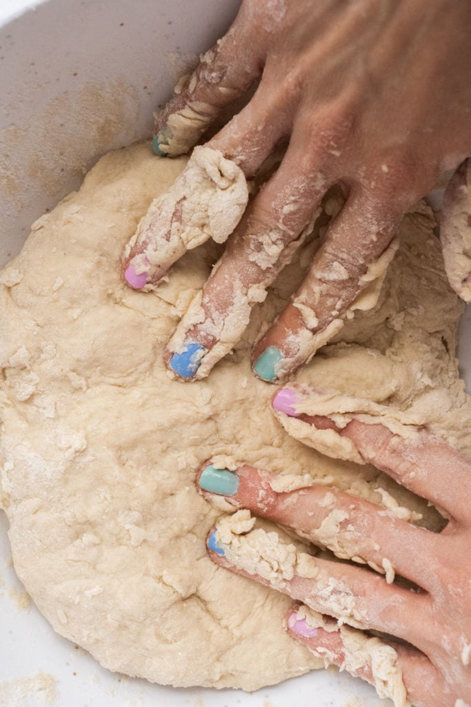 painted nails on hand kneading dough