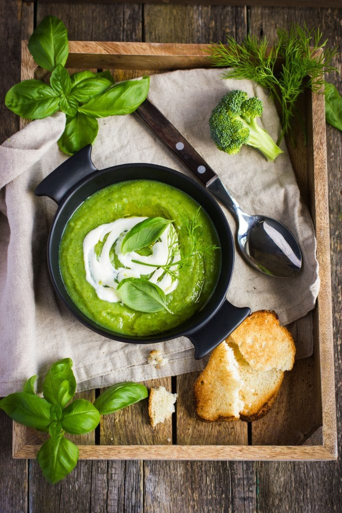 Cream of Broccoli Soup in black bowl with bread on side