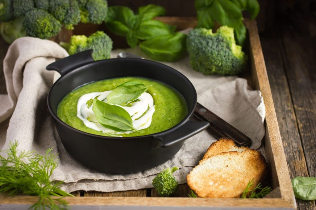 Cream of Broccoli Soup in bowl being served for dinner with bread