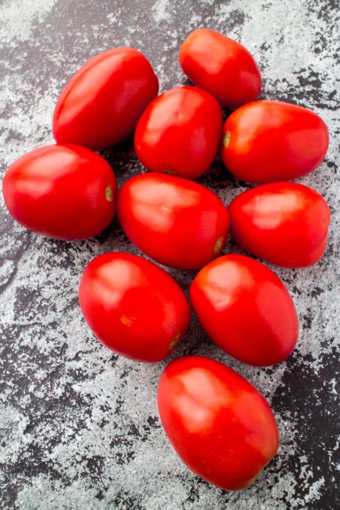 fresh garden tomatoes sitting on table.
