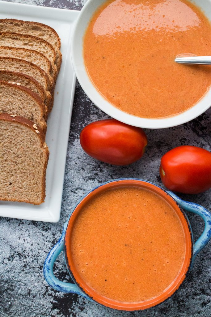 bowls of fresh tomato soup on table with plate of bread next to it.