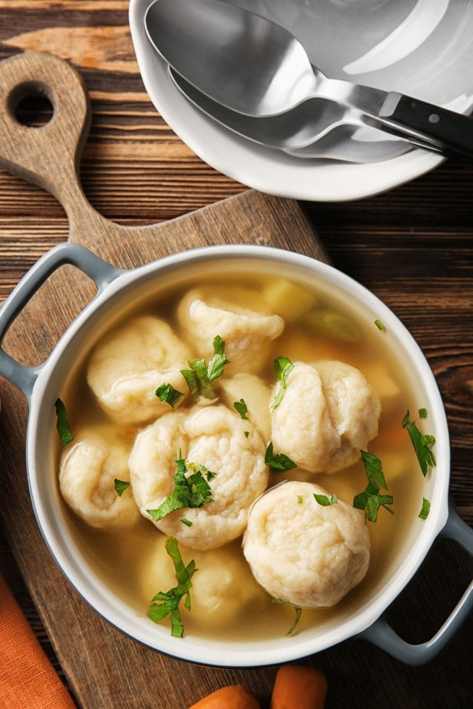 homemade dumplings served in chicken soup broth on brown cutting board