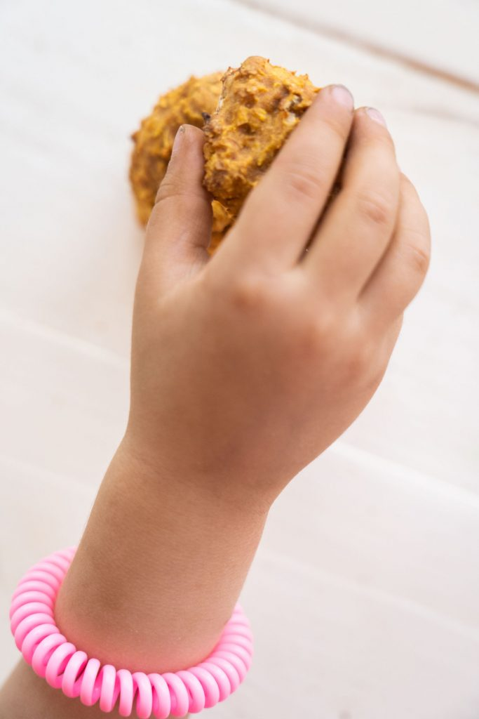 kids hand reaching in and taking healthy carrot cookie off white table