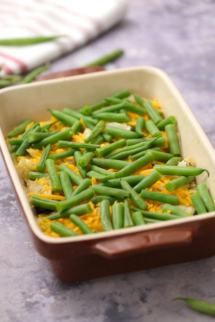 green beans on top of cheese in baking dish