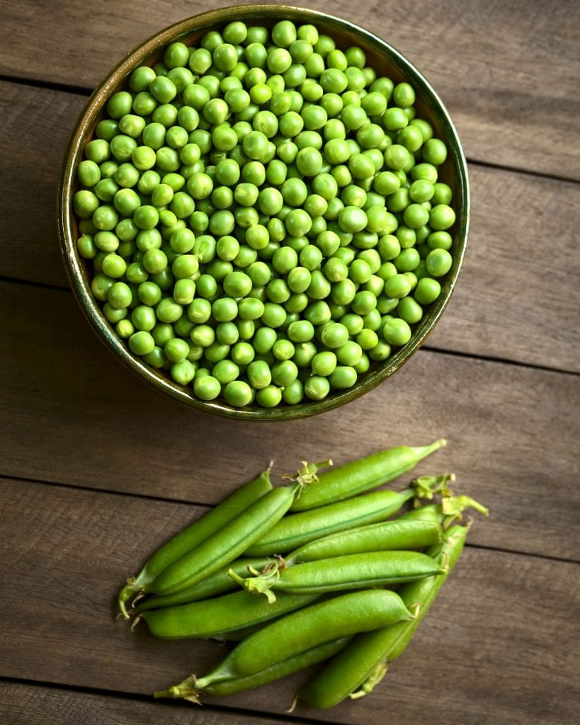 bowl of fresh peas on wooden brown table