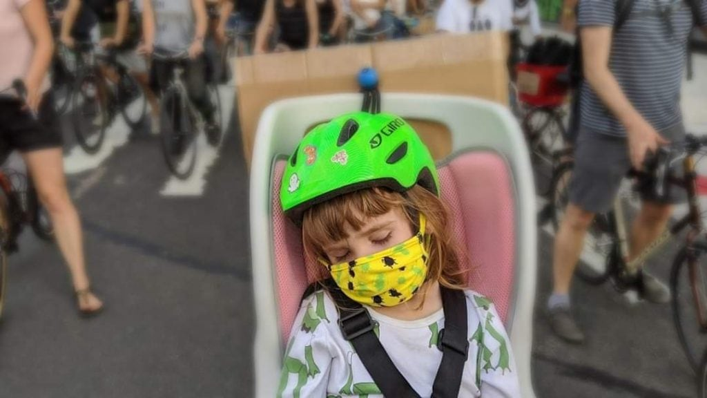 little girl riding bike with dad at bike protest in nyc