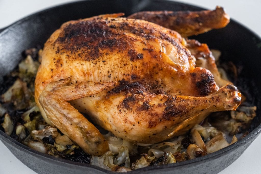 cooked roasted chicken sitting on top of cabbage in cast iron skillet
