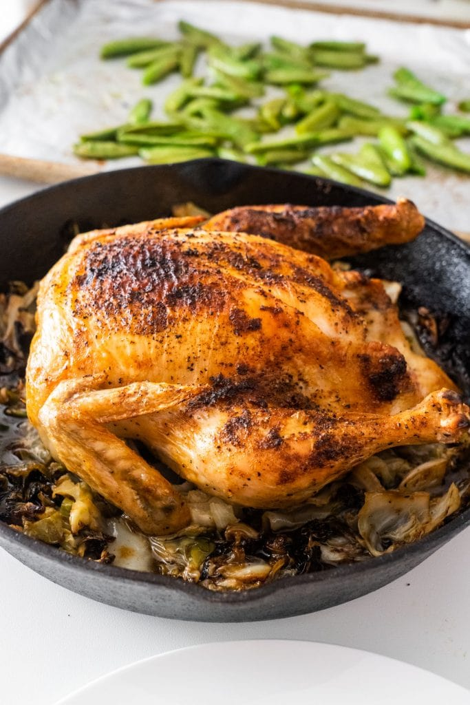 roasted whole chicken in cast iron skillet with cabbage and roasted peas on white counter top