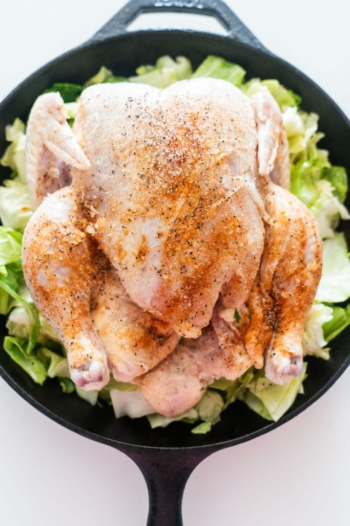 whole chicken with seasonings placed on top of cabbage in cast iron skillet