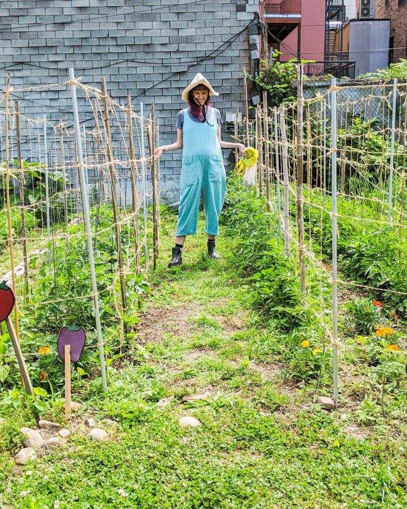 woman wearing blue jumpsuit in vegetable garden