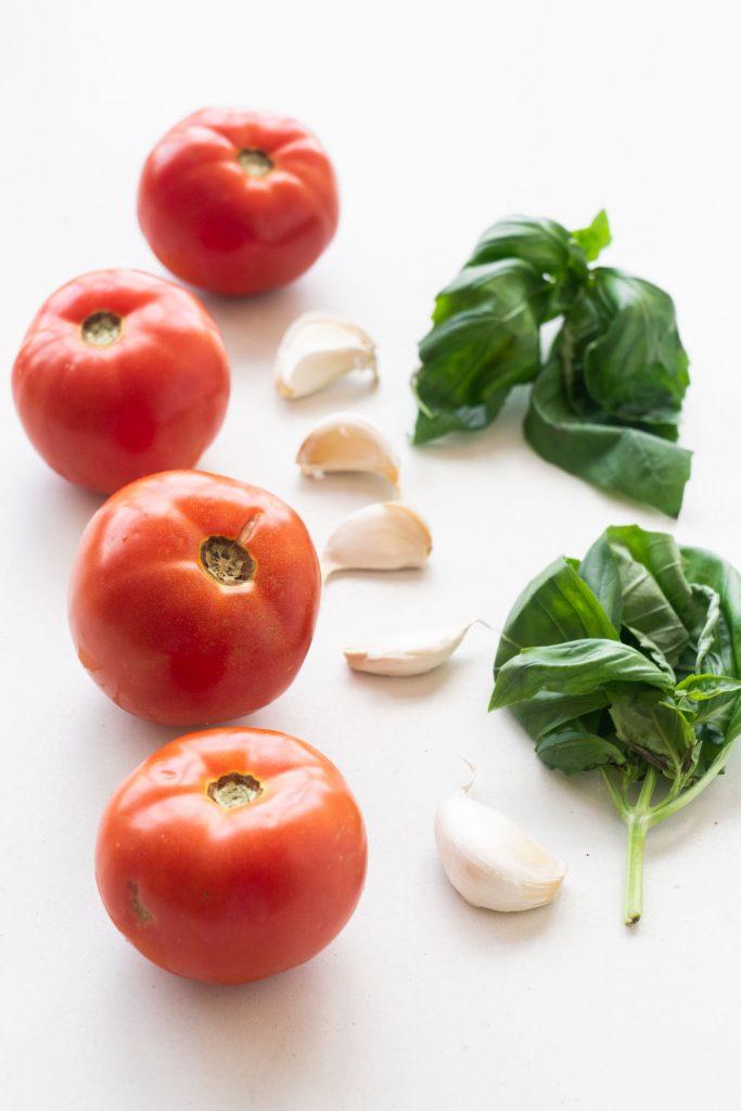 tomatoes, garlic and basil on white background