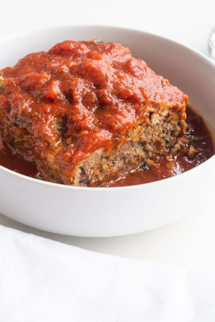 ground beef meatloaf with tomato sauce on top in white serving dish