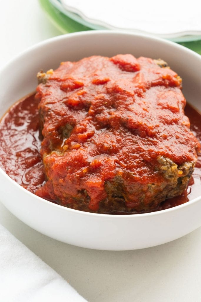 ground beef with savory tomato sauce on top of it in white serving dish on white table