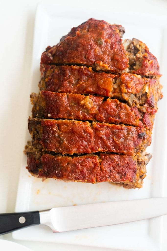 baked cheesy meatloaf sliced into pieces on white plate