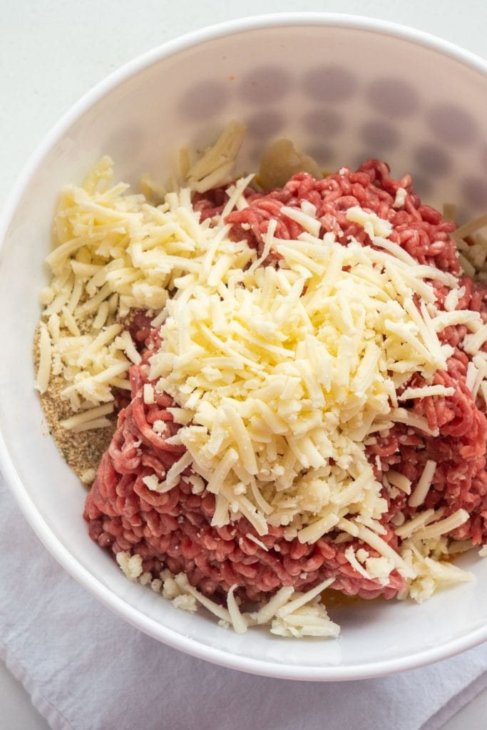 ground beef, cheddar cheese, bread crumbs and eggs in white bowl