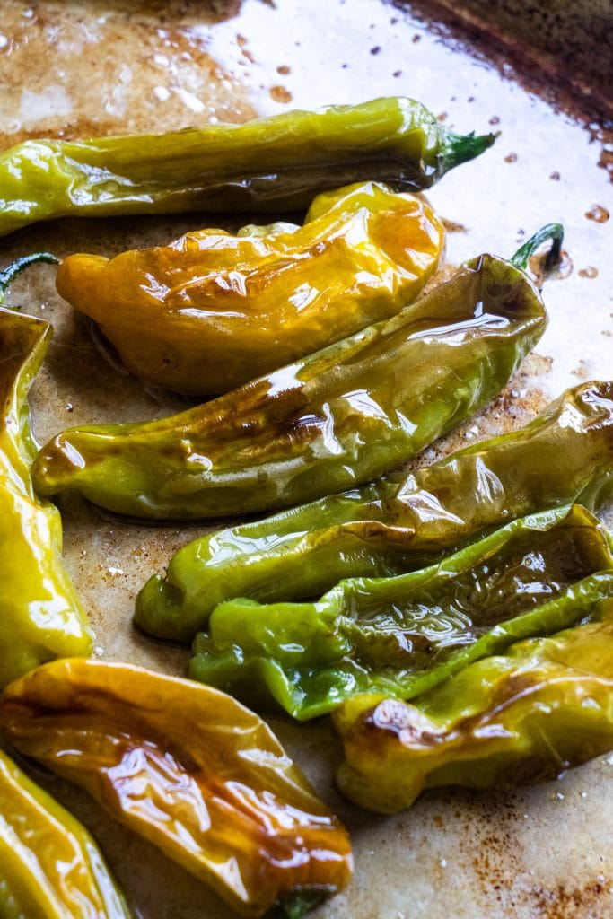 blistered shishito peppers on baking sheet out of the oven