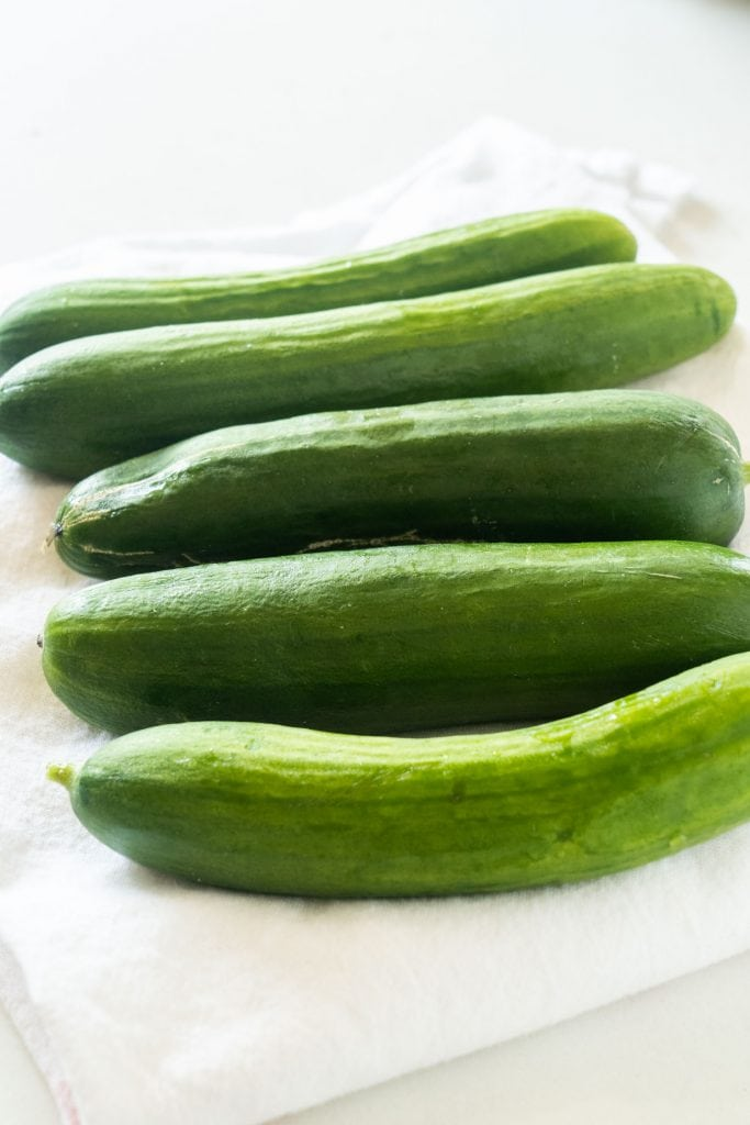 cucumbers laying on paper towel  on white background