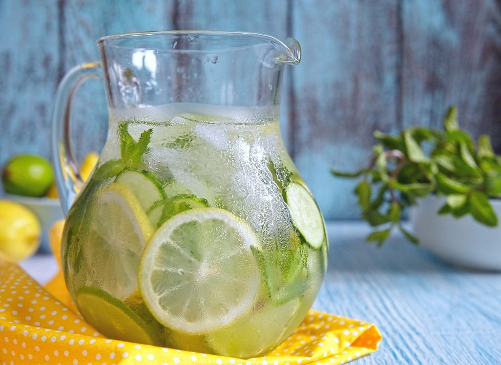 pitcher of ice water with sliced cucumbers and lemon