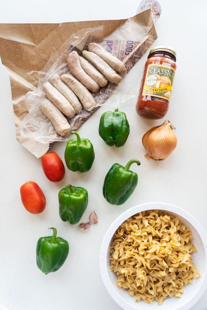 sweet italian sausage links, green peppers, tomatoes, onion, garlic, pasta sauce and egg noodles in bowl on white table