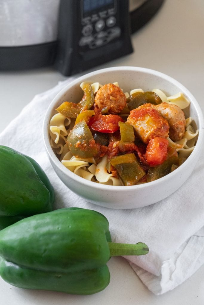 bowl of sausage and peppers on top of egg noodles in front of slow cooker