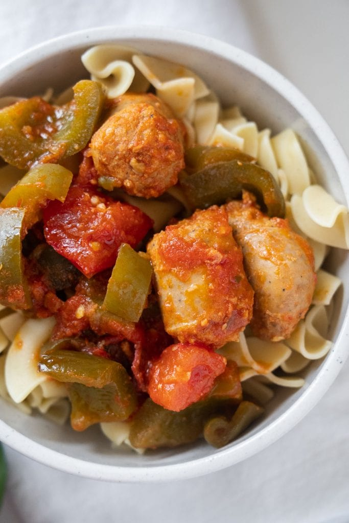 white bowl filled with sweet italian sausage and peppers on top of egg pasta
