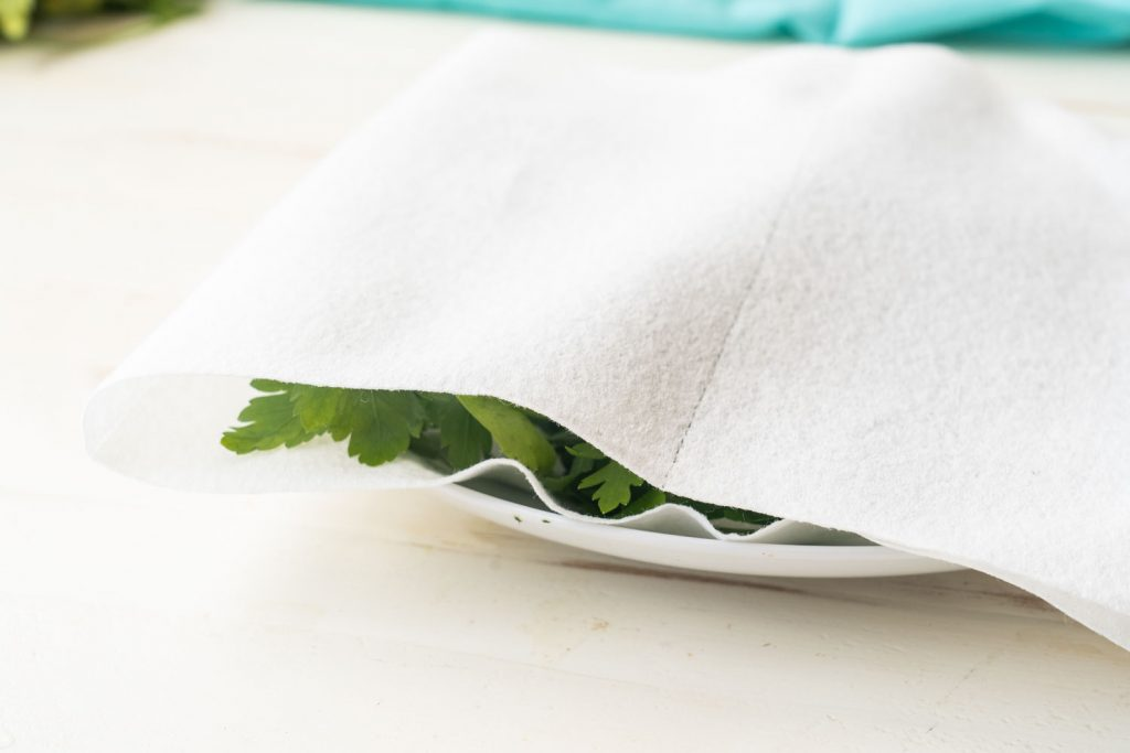 parsley being dried in microwave on paper towels