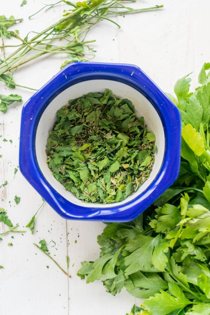 dried parsley in blue bowl on white table