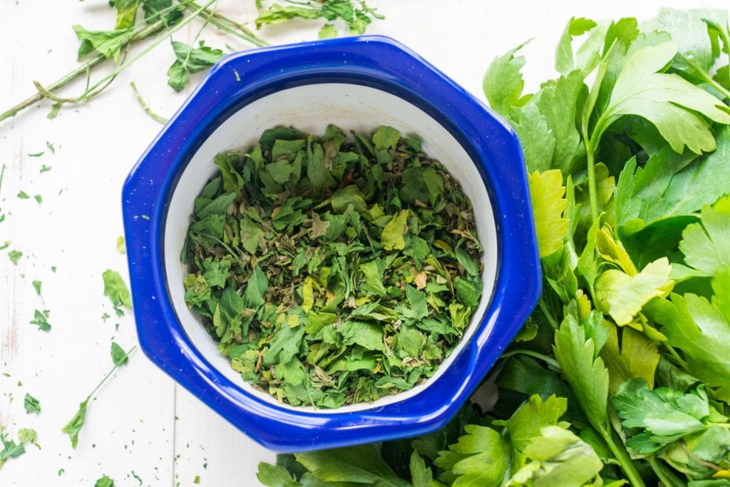 dried parsley in blue bowl on white background