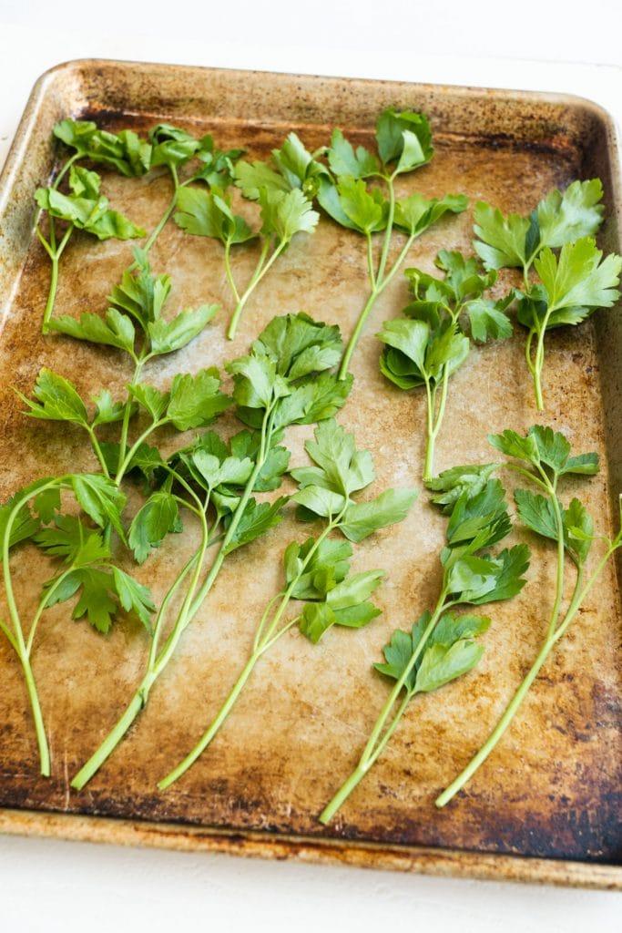 fresh parsley leaves on baking sheet