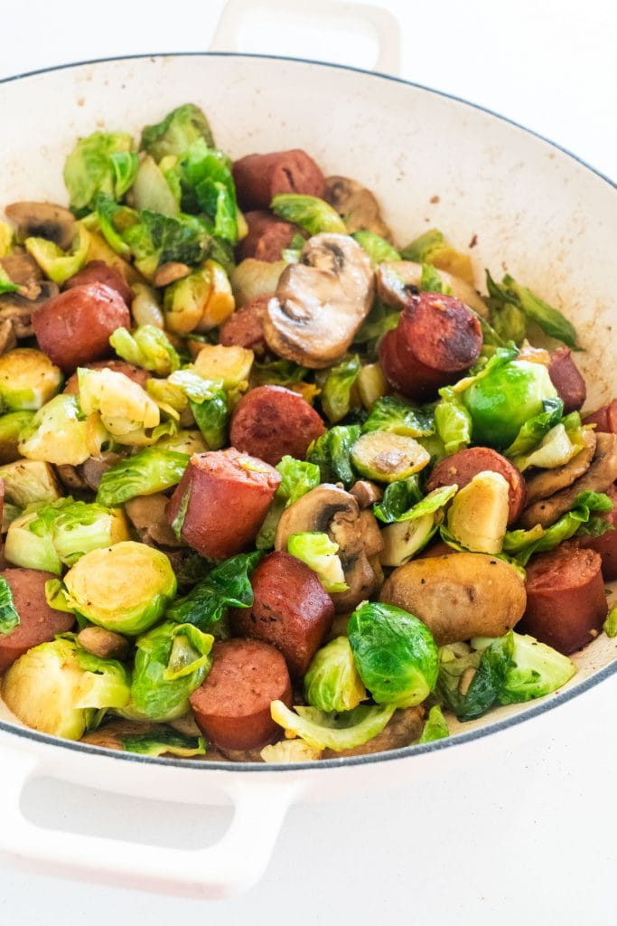 kielbasa, brussels sprouts and mushrooms in white skillet cooked