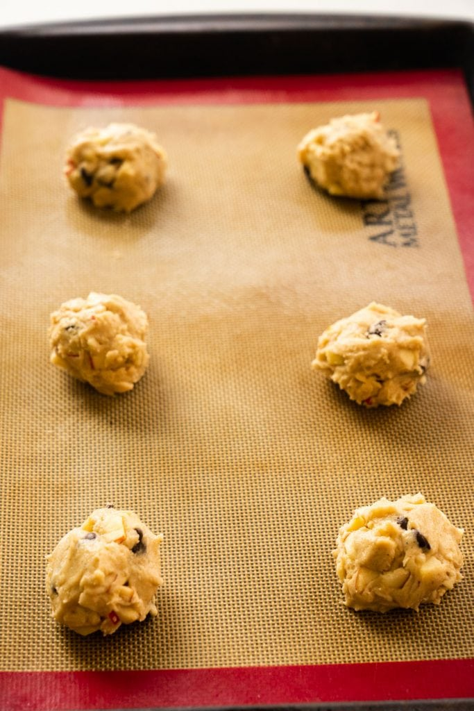 balls of uncooked cookie dough on silicone baking mat on cookie sheet