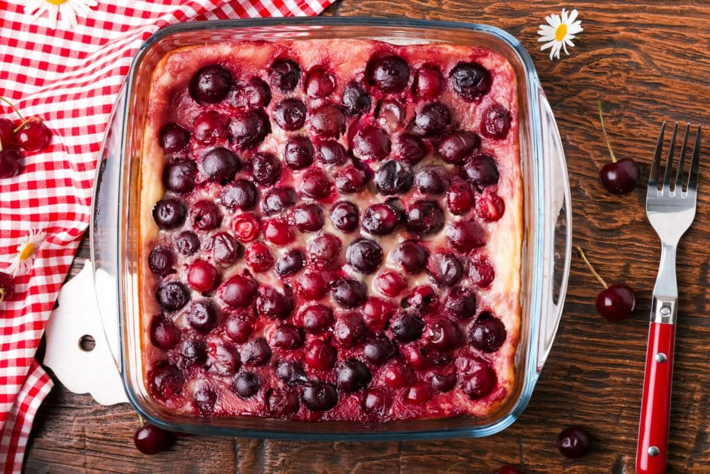 cherry clafoutis in 9x9 glass baking pan on wooden background