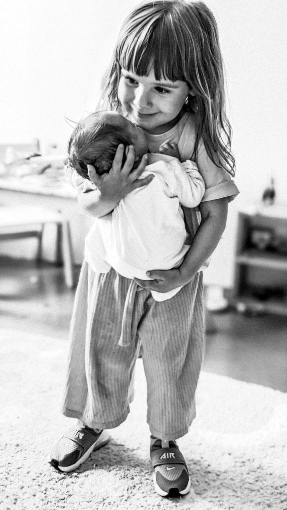 little girl holding baby, black annd white photo