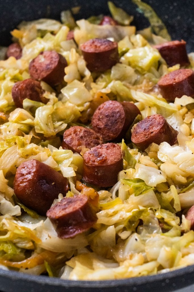 chopped up sausage with cabbage and onions in black skillet