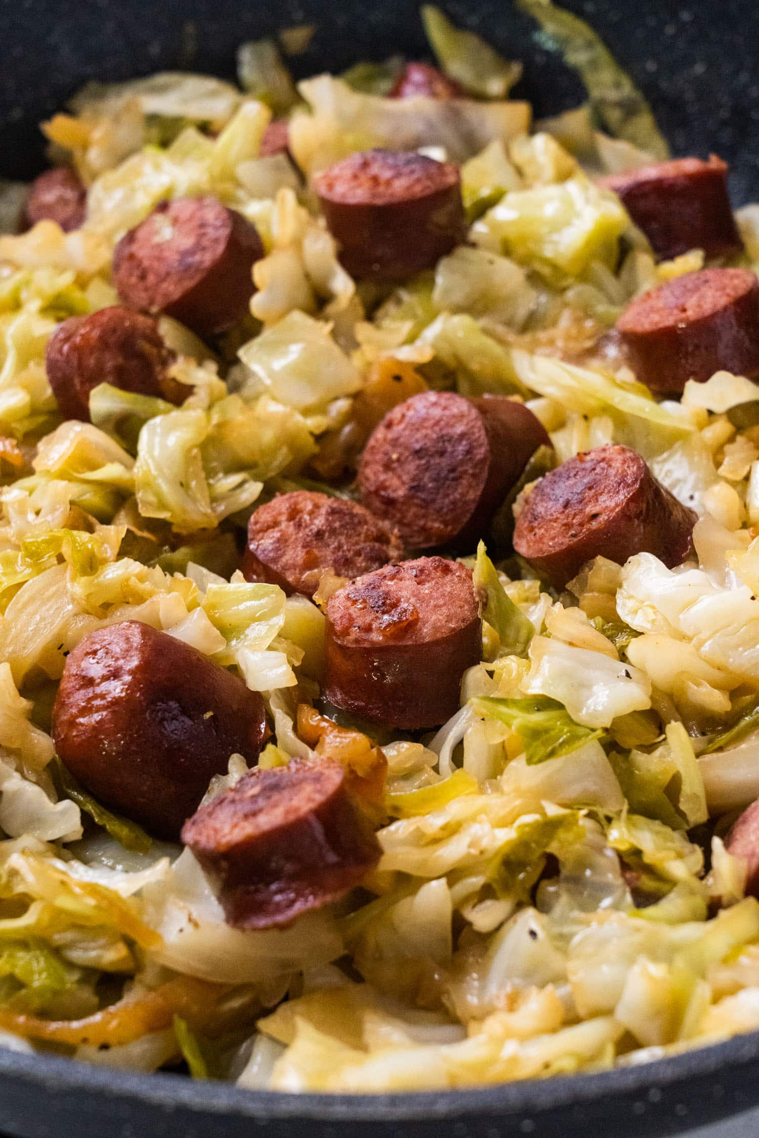 chopped up sausage with fried onions in skillet with wooden spoon