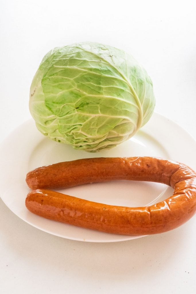 head of cabbage and sausage on white plate