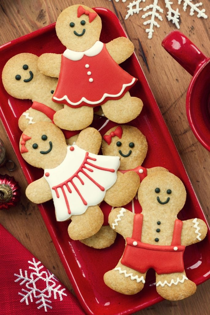 gingerbread men and women cookies on red plate wearing dresses and bows