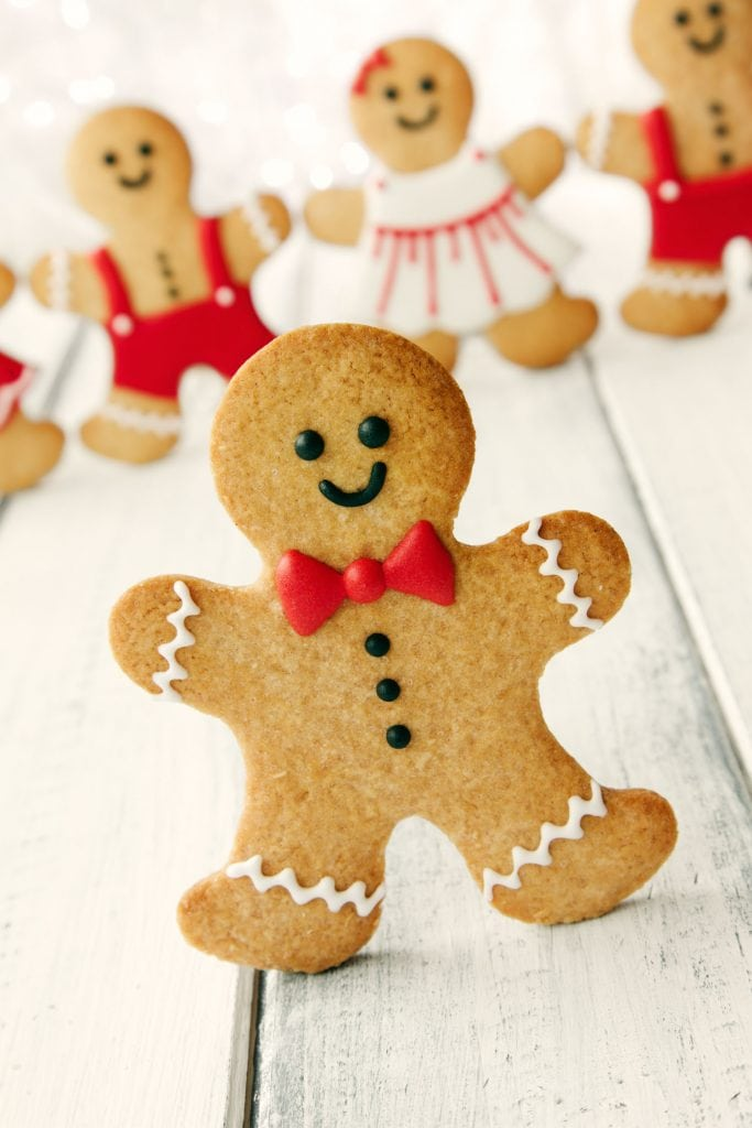 gingerbread man cookie standing wearing red bow while other cookies stand in background