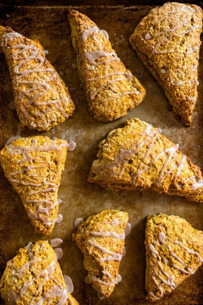 8 pumpkin scones with vanilla cinnamon glaze on top of them on baking sheet