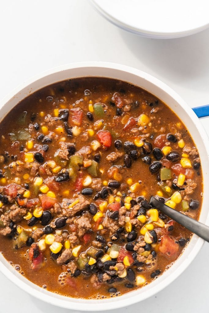 pot filled with taco soup on white table, black spoon in pot