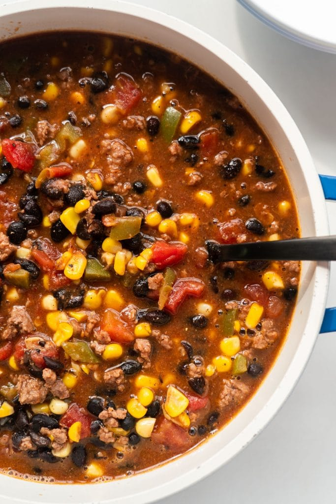 taco soup in blue soup pot with black spoon