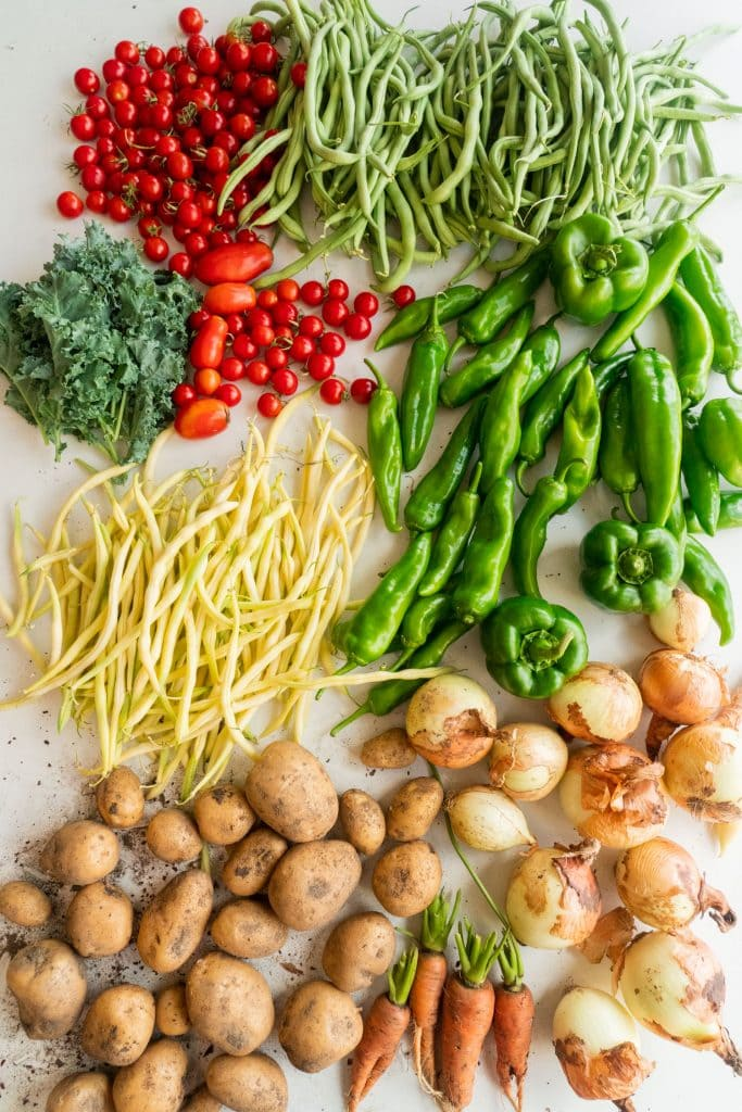 tomatoes, green beans, kale, peppers, beans, onions and potatoes on white table
